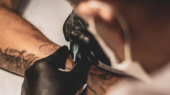 Zowel klant als tatoeëerder beschermen hun mond en neus tijdens de sessie